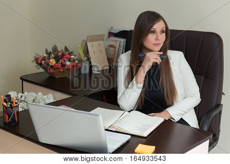 Pretty Young Office Woman Sitting At Her Desk With Notes And Laptop, Showing A Pensive Facial Expres
