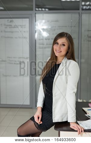 Portrait Of Beautiful Businesswoman Leaning Against Wall In Office.