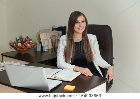 Portrait Of A Pretty Secretary Sitting At Her Desk And Smiling.