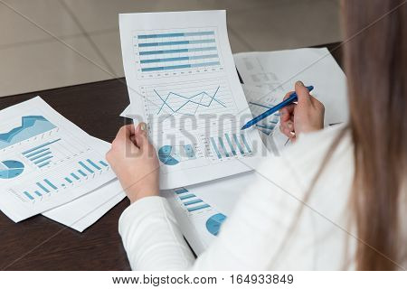 Businesswoman Reading Business Graph Or Analysis Chart At Office Desk.
