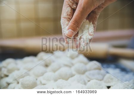 Man's hand sprinkling flour over a cutting board