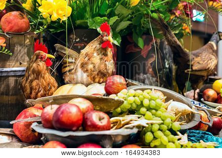 Colorful rooster and hen near fruit and grapes still-life rustic background