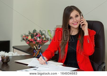 Beautiful Smiling Business Woman Working At Her Office Desk With Documents And Talking On The Phone.