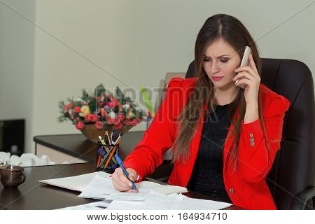 Beautiful Business Woman Working At Her Office Desk With Documents And Talking On The Phone.