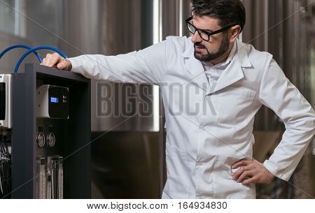 High responsibility. Handsome delighted smart man controlling brewing mechanism while working in brewery and wearing glasses.