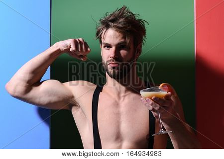 young handsome bearded sexy macho man with stylish beard shows biceps and triceps on athletic body in suspenders holding glass of alcoholic cocktail on colorful background