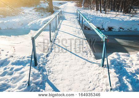 Small pedestrian bridge over the frozen creek