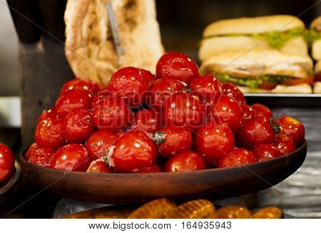 juicy marinated tomatoes in a wooden plate on the counter