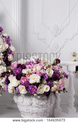 flowerpot with roses near a wall and decorative balcony indoor