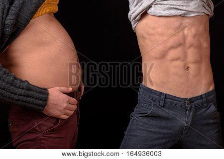 two friends showing paunchy and slim bellies with bare torso and six packs or abs in studio on black background