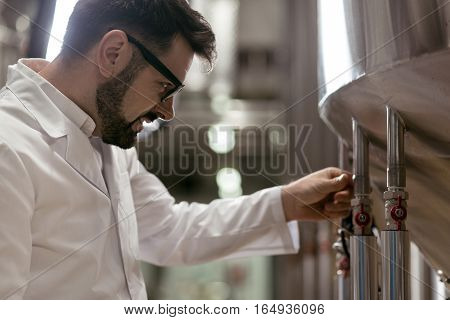 Make it good. Handsome smart delighted man working as a brewer while using brewing mechanism and making beer.