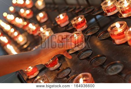 Hand Of Young Girl  Turns On A Red Candle In Church