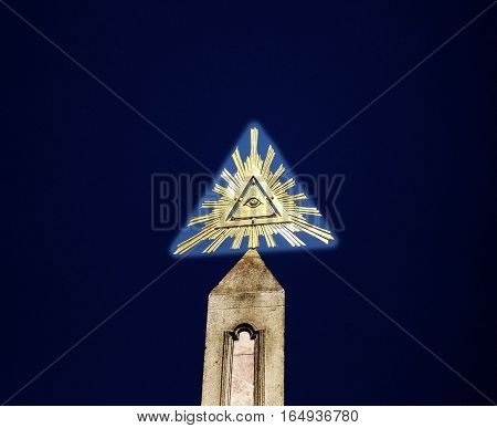 Eye of Providence over a tall obelisk by night