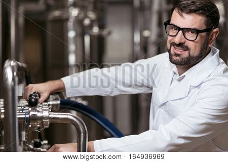 Love my job. Overjoyed young delighted man posing in brewery while making beer and working.