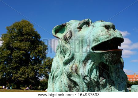 Rosenborg Palace in Copenhagen Denmark. Sculpture of lion against Rosenborg castle and blue sky. Statue is situated in front of bridge. Lion meditatively wistfully looking away.