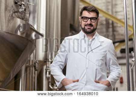 Happy worker. Overjoyed young delighted man posing on beer factory while working and smiling.