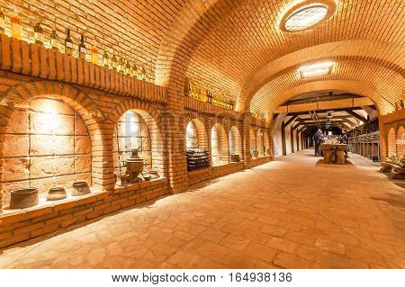KVARELI, GEORGIA - OCT 3, 2016: Old grape wine cellar Khareba Winery with many bottles in unique underground tunnel on October 3, 2016. The tunnel was opened in 1962 for the World Wine Congress