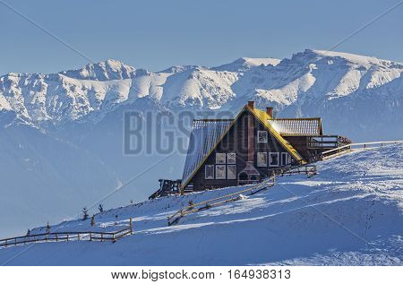 Majestic alpine scenery with rustic wooden chalet and snowcapped mountain ridge of the Bucegi massif during winter season in Transylvania region Romania. Scenic touristic retreat destinations.