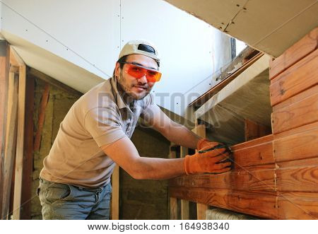 Man Measuring Rail At Home During Construction