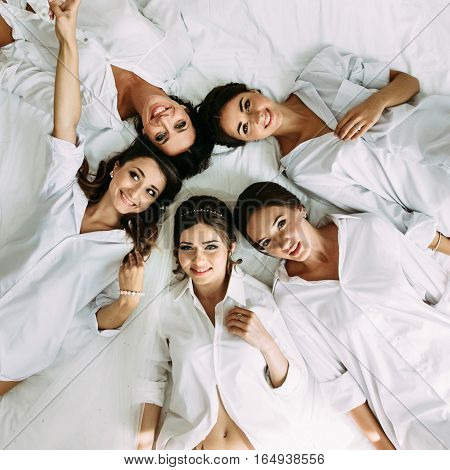 Bride And Bridesmaids Are Lying On The Bed