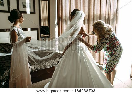 Mom is helping to dress a bridal gown