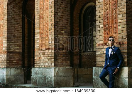 Stylish groom next to the wall in the wedding day