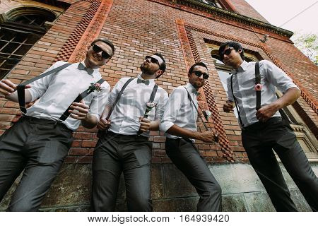 Stylish groomsmen in the suspenders and bow-ties
