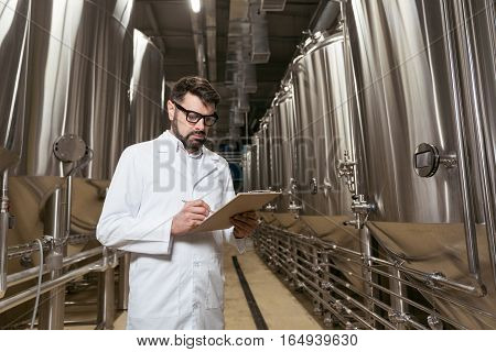 Be involved. Handsome young delighted man making notes while working in brewery and spending time on factory.
