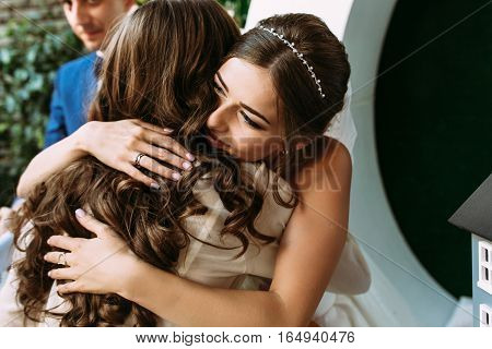 Bride is embracing her friend on the wedding