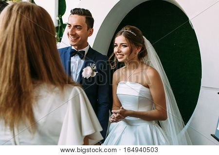 Joyful young married couple is meeting guests