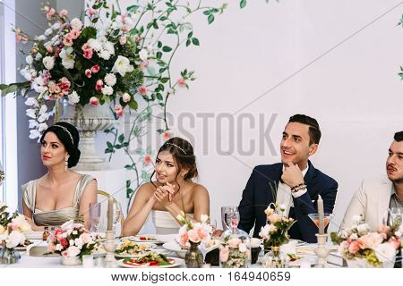 Bride with the groom are watching on the guests