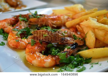 Grilled shrimps with potato on a plate in restaurant on Cyprus