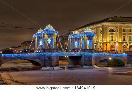 SAINT-PETERSBURG, RUSSIA - JANUARY 12, 2017: Night illumination of The Lomonosov Bridge across The Fontanka River. Winter view. The bridge was built in 18 century
