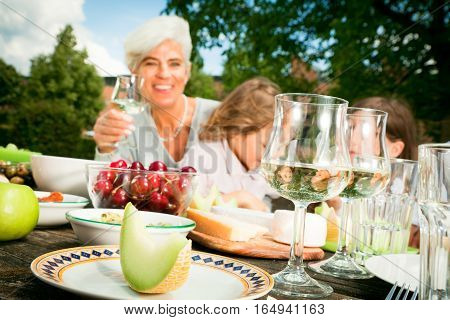grandmom and their grandchildren are having a picnic in the garden. focus is on the wine glass and the melon in the foreground, the people in the back are out of focus.