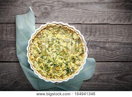 Spinache quiche, gluten free on a wooden surface