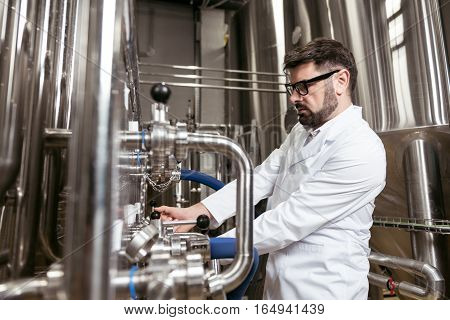 Good worker. Hardworking young handsome man using brewing mechanism while spending time at factory and making beer.