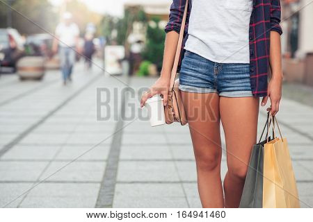Unrecognizable young woman carrying shopping bags and a coffee cup while walking down a sidewalk in the city