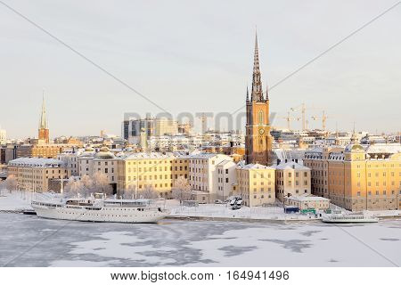 STOCKHOLM - JAN 08 2017: Beautiful boat and old buildings at Riddarholmen lit with warm light a cold winter morning ice on the sea. January 08 2017 in Stockholm Sweden