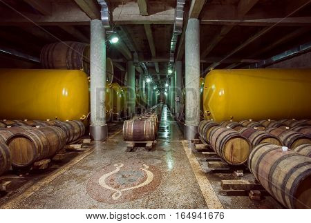 KVARELI, GEORGIA - OCT 3, 2016: Wooden barrels and metal cistern with wine inside old cellar of Kindzmarauli Corporation Wine House on October 3, 2016. Winery produces 25 varieties of wine and 10 brandies