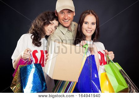 studio shot of three young people enjoying a sale event - and if you cant join them at the mall, mr. deliveryboy will bring you the stuff right to your door