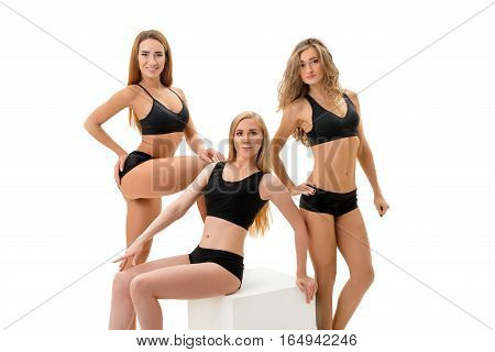 Young long haired girls in sexy slinky black sports briefs and tops posing in studio