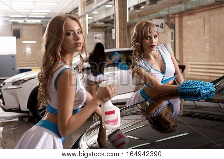 Sexy long haired girls in formula one style tops and mini skirts posing with sponges and sprayer near car at carwash