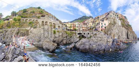 MANAROLA TOWN, RIOMAGGIORE, LA SPEZIA, LIGURIA, NORTHERN ITALY - 9 August, 2015: View of the colourful houses on surrounding hills sea shore balconies and windows. Part of the Cinque Terre National Park and a UNESCO World Heritage Site.