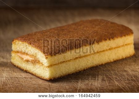 Sponge cake with fruit cream over wooden background