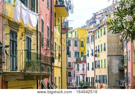Riomaggiore village La Spezia province Liguria northern Italy. View of the colourful houses on steep hills and laundry on balconies. Part of the Cinque Terre National Park and a UNESCO World Heritage Site.