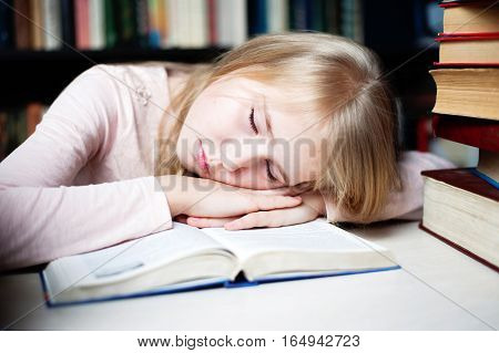 Cute Little Girl Lying On Table While Doing Her Homework.
