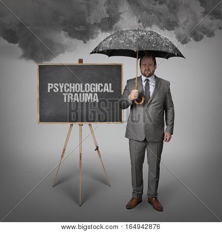psychological trauma text on blackboard with businessman holding umbrella