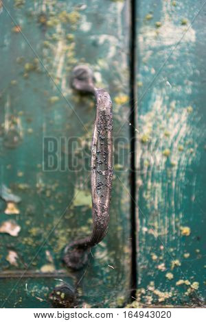 weather-beaten door handle on an old cart in the rain