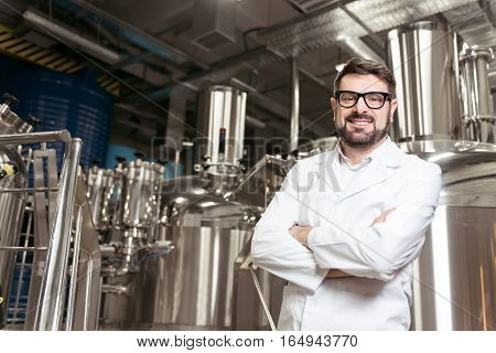 Be happy about it. Smiling handsome young man posing with brewing mechanisms while spending time at beer factory and working.