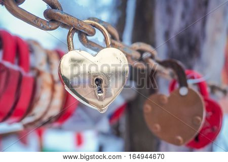 Golden padlock in the shape of a heart on a chain Vicino outdoors in winter. Valentine's Day Concept